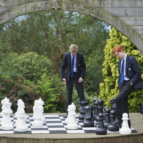 students playing giant chess outside
