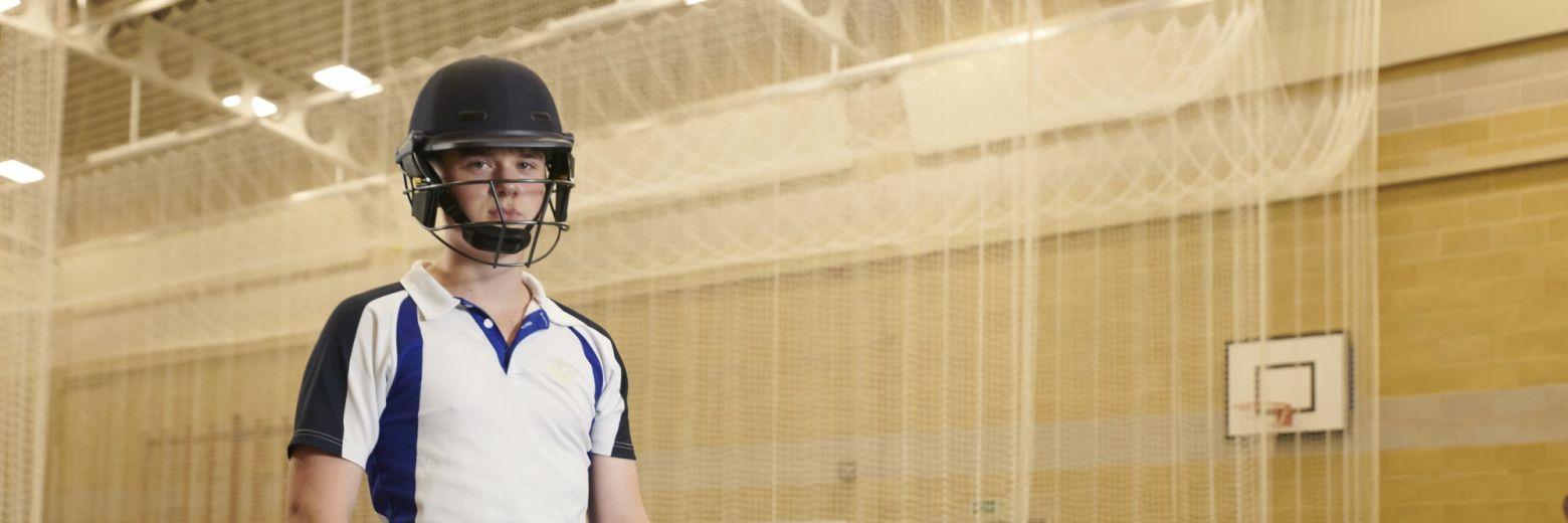 school student wearing cricket kit in sports hall