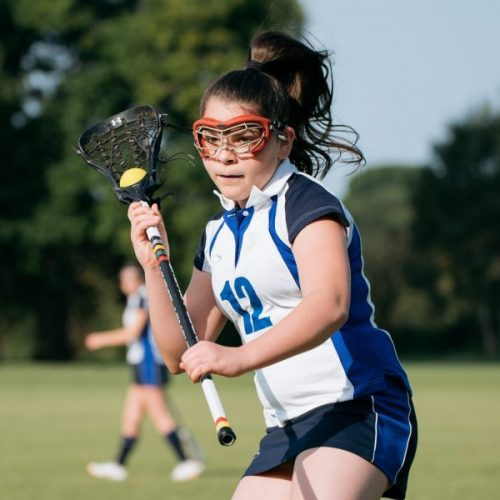 school girl holding a lacrosse stick